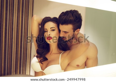 Sexy young couple in mirror at home, vintage style - stock photo