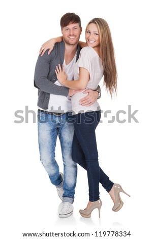 Sexy young couple in trendy casual clothes standing close together in a loving embrace smiling at the camera isolated on white - stock photo