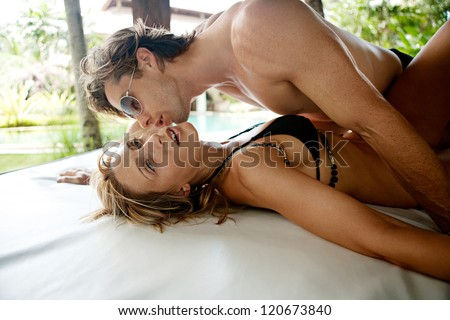 Sexy young couple kissing and being passionate while lounging on a lounger bed in the tropical garden of a holiday hotel exotic garden, near a swimming pool,