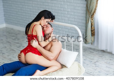 Sexy young couple kissing and playing in bed.  - stock photo
