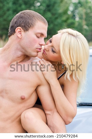Sexy young couple kissing on the car's hood.