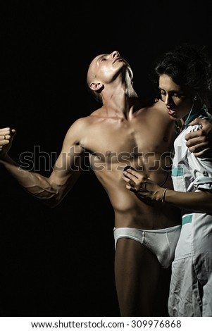 Sexy young couple of undressed man in pants with strong muscular beautiful body and pretty brunette nurse in white smock with stethoscope standing on black studio background, vertical picture