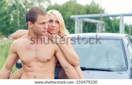 Sexy young couple siting on the car's hood. - stock photo