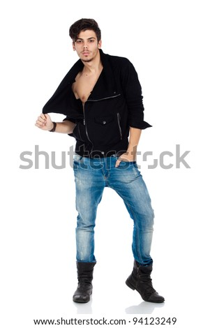 Sexy young fashion model wearing jeans, boots and a black jacket. Isolated on white background. Studio vertical image.
