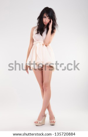 sexy young fashion woman holding her hand on her temples and her feet crossed while looking at the camera. on gray background - stock photo