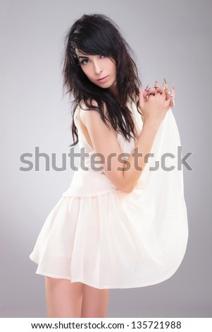 sexy young fashion woman is holding her dress with interleaved fingers and looking provocatively at the camera. on gray background - stock photo