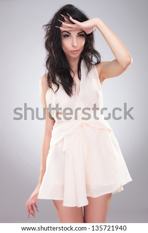 sexy young fashion woman looking far away with her hand above her eyes. on gray background - stock photo
