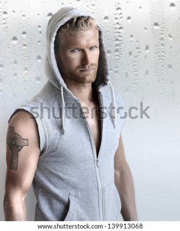 Sexy young fit man in hooded training vest against modern studio background - stock photo