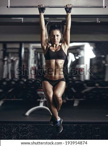 sexy young fitness girl pulls up in the gym. Brunette fitness woman in black sport wear with perfect fitness body in gym performing abdominal exercises on the horizontal bar - stock photo