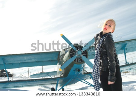 sexy young girl next to the pilot vintage aircraft - stock photo