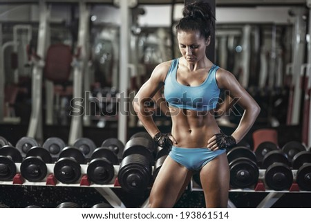 sexy young girl resting after dumbbells exercises. Fitness woman in blue sport wear with perfect fitness body resting in gym - stock photo