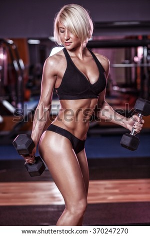 sexy young girl with perfect abs and body doing exercises with dumbbells. Fitness blonde woman biceps workout in gym - stock photo