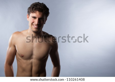 Sexy young guy with shirt off showing abdominal and arm muscles in studio against a grey background. - stock photo