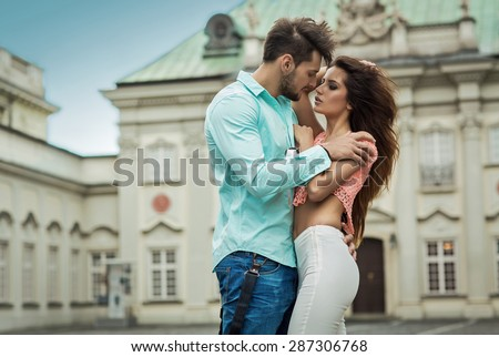 Sexy young kissing couple in love. Outdoor shot on blurred background - stock photo