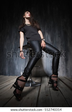 Sexy young lady dressed in black fashionable clothes