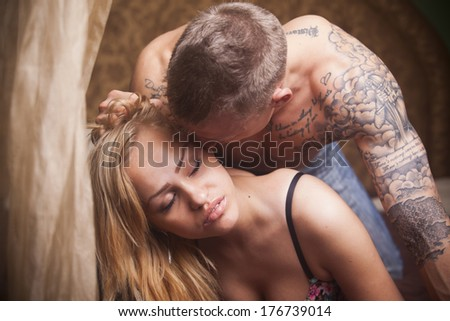 Sexy young lingerie couple embracing on the bed - stock photo