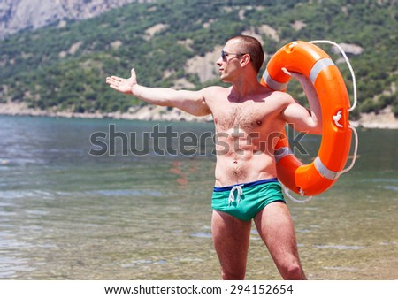 Sexy young man body builder with six pack is posing on the beach with orange lifebuoy ring - stock photo