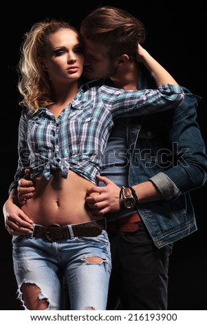 Sexy young man embracing his girlfriend from the back while she holds her hand behind his head. on black background - stock photo