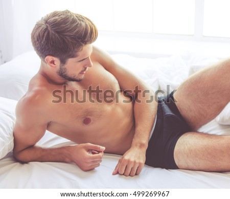 Sexy young man in black briefs is lying in bed