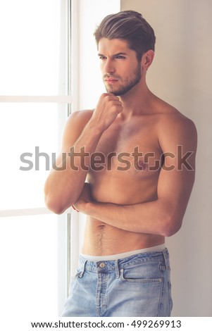 Sexy young man in jeans and with bare torso is looking away and rubbing his chin while standing near the window at home