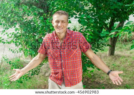 Sexy young man in rain. Pleasure cool rain in summer on background of trees