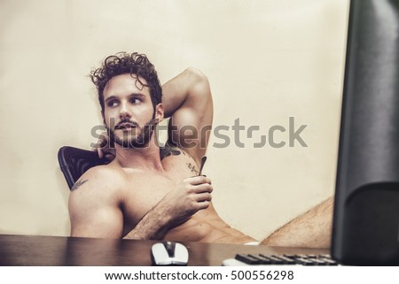 Sexy young man in underwear sitting with cup of coffee at desk