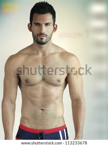 Sexy young man portrait against modern background - stock photo