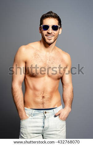 Sexy young man with beautiful muscular body looking to camera and smiling invitingly. Studio shot. - stock photo