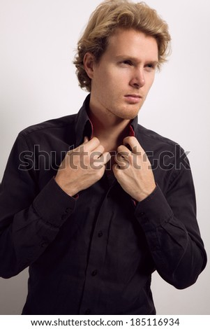 Sexy young man with blonde hair, dressed in black shirt, with hands on his collar, looking away - stock photo