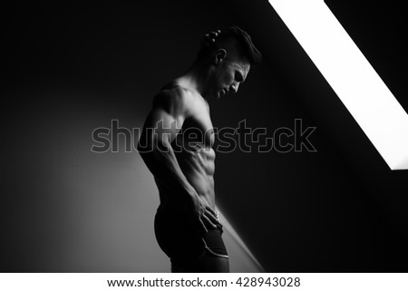 Sexy young man with muscular body and bare torso posing in shorts near window, black and white