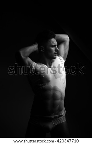 Sexy young man with muscular body in wet shirt posing in trunks near window