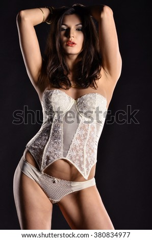 Sexy young model in white lingerie. Photo in the dark studio.