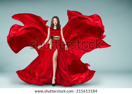 Sexy young motion woman in long red evening fluttering fashion dress flying over background - stock photo