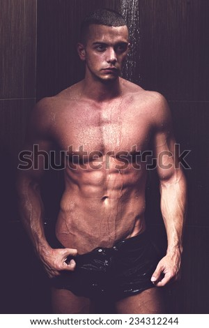 Sexy young muscle man in a shower wearing dark underwear - stock photo