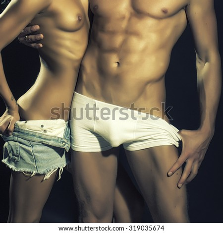 Sexy young naked couple of muscular boy in white underwear and girl with straight beautiful body in jeans shorts standing close to each other in studio on black background, square photo - stock photo