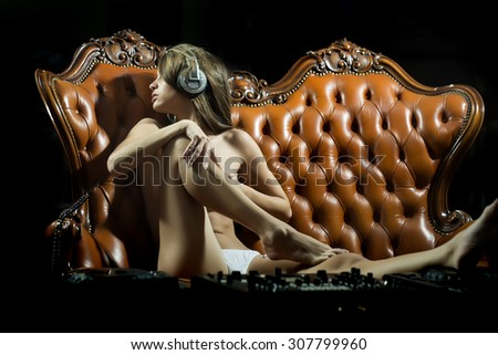 Sexy young naked dj woman in white panties and headphones with bare chest and nipples sitting at table with mixer console on brown leather royal sofa in night club, horizontal picture - stock photo