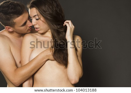 Sexy young passion couple on gray isolated background - stock photo