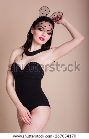 Sexy young pretty woman is wearing bunny ears mask with lace veil and black body over studio flash light - stock photo