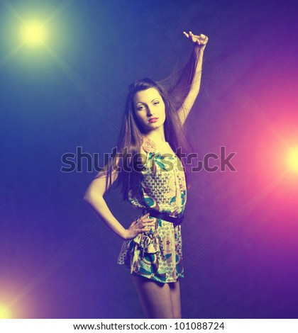 Sexy young self-confident brunette girl dancing in discolight - stock photo