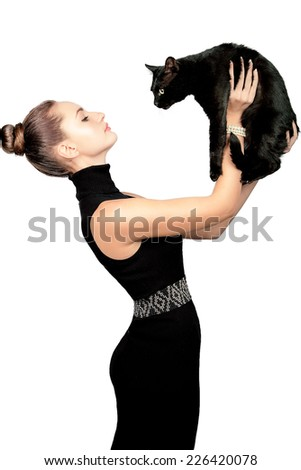 Sexy young skinny woman in black dress and pearl jewelry and black cat looking at each other. Studio shoot. - stock photo