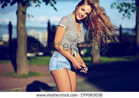 sexy young stylish smiling woman girl model in bright modern cloth with perfect sunbathed body outdoors in the park in jeans shorts with flying elevated hair in air - stock photo