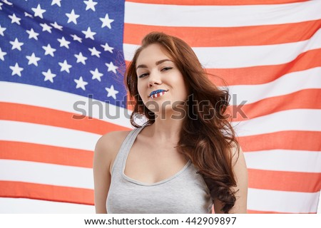 Sexy young white brunette girl celebrating National Independence Day on 4th of July in United States of America with painted face. Attractive model with toothy smile, flag on the background