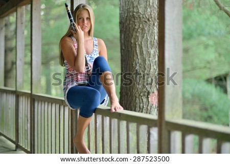 Sexy young woman - barefoot - on a wooden porch with clarinet - country music series - stock photo