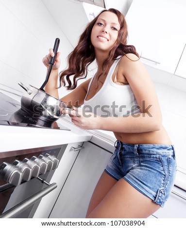 sexy young woman cooking in the kitchen at home - stock photo