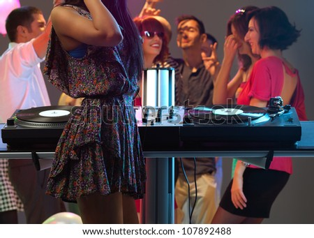 sexy, young woman dj, entertaining the crowd in a night club