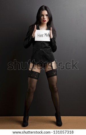 """Sexy young woman holding a paper with the text message """"Hire me"""". - stock photo"""