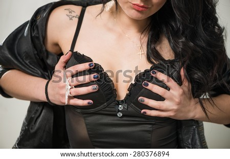 sexy young woman holding corset at breast with hands