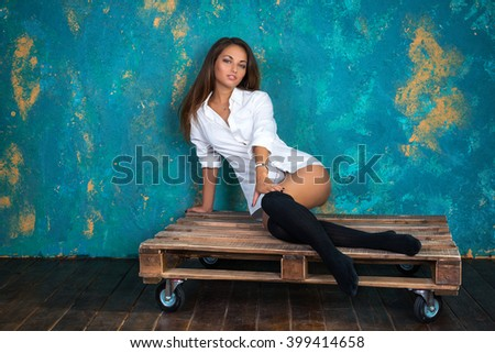 Sexy young woman in a man's shirt and leg warmers sitting on wooden pallet on grunge wall background - stock photo