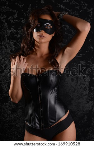 Sexy young woman in a mysterious mask and corset - stock photo