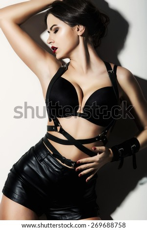 Sexy young woman in black erotic lingerie studio light background